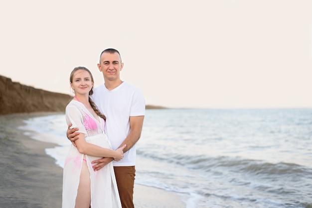Junges verheiratetes paar auf der seeküste. ehemann umarmt seine schwangere frau. zeit vor sonnenuntergang