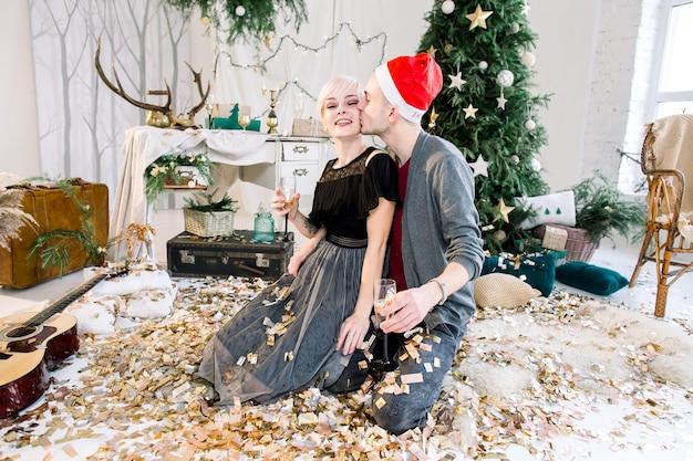 Junges verliebtes paar, das auf boden nahe weihnachtsbaum sitzt, der goldenes konfetti wirft