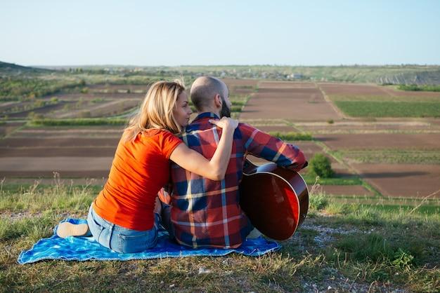 Junges verliebtes paar, das auf dem park sitzt, während diese junge gitarre gitarre in der sonnenuntergangszeit spielt.