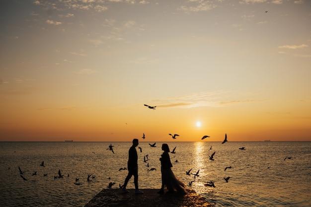 Junges verliebtes paar, das auf dem sonnenaufgang des strandes und den fliegenden möwen geht.