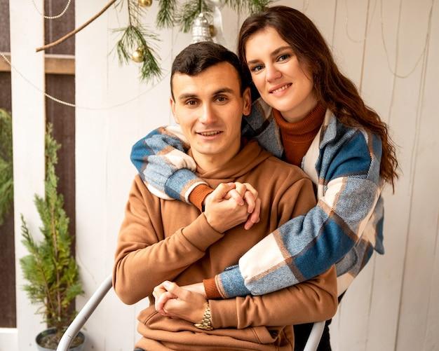 Junges verliebtes paar, das auf der veranda sitzt. sie umarmen sich und lächeln.
