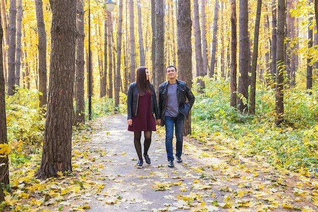 Junges verliebtes paar, das händchen hält und an einem sonnigen herbsttag durch einen park geht?