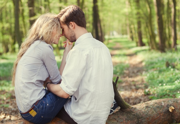 Junges verliebtes paar, das im frühjahr im park sitzt