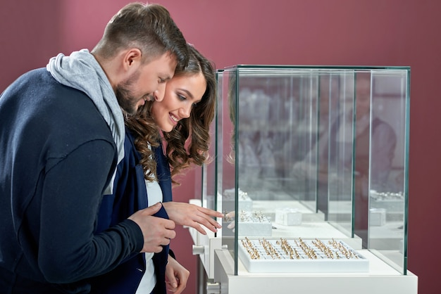 Junges verliebtes paar, das ringe im juweliergeschäft kauft
