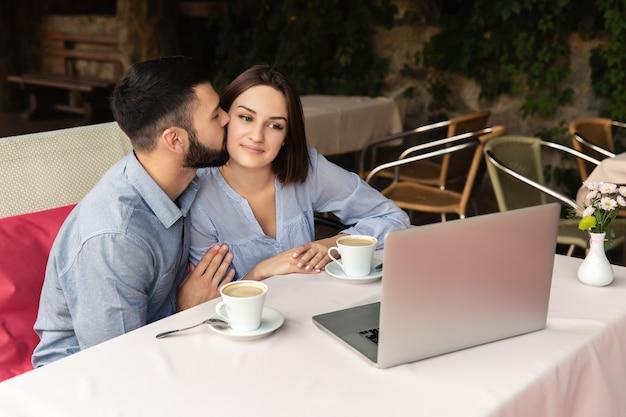 Junges verliebtes paar, das von zu hause aus arbeitet, mann küsst frau auf die wange, und sie schaut auf den laptop drinnen