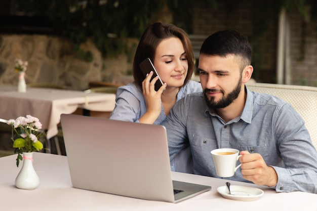 Junges verliebtes paar, das von zu hause aus arbeitet, mann und frau, die am tisch sitzen und drinnen am laptop arbeiten