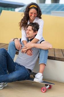 Junges verliebtes paar hat spaß im urbanen skatepark sitzen kuscheln in longboard glücklich lachend umarmen