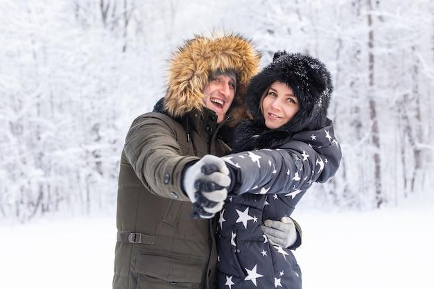 Junges verliebtes paar hat spaß im verschneiten wald aktive winterferien