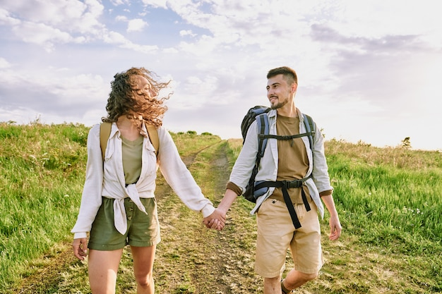 Junges verliebtes paar in der freizeitkleidung, die spricht, während sie landstraße gegen bewölkten himmel am sommertag hinunter bewegt und einander ansieht