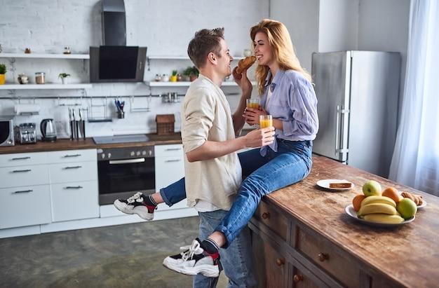 Junges verliebtes paar in der küche. der typ füttert das mädchen mit einem croissant. romantisches frühstück.