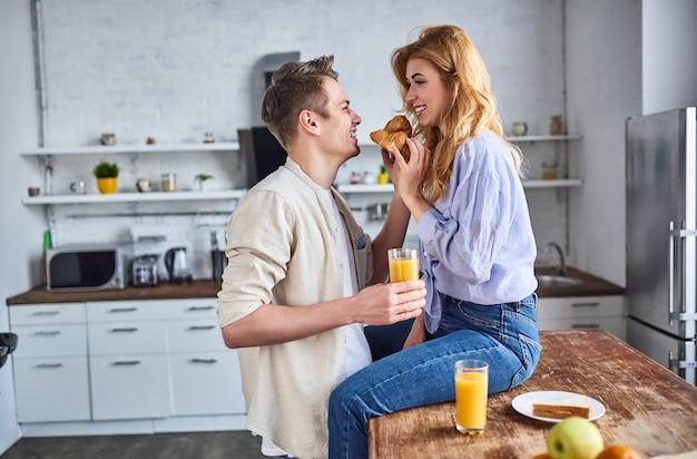 Junges verliebtes paar in der küche füttert sich mit einem croissant. romantisches frühstück.