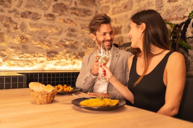 Junges verliebtes paar in einem restaurant, röstet die gläser wein und feiert valentinstag