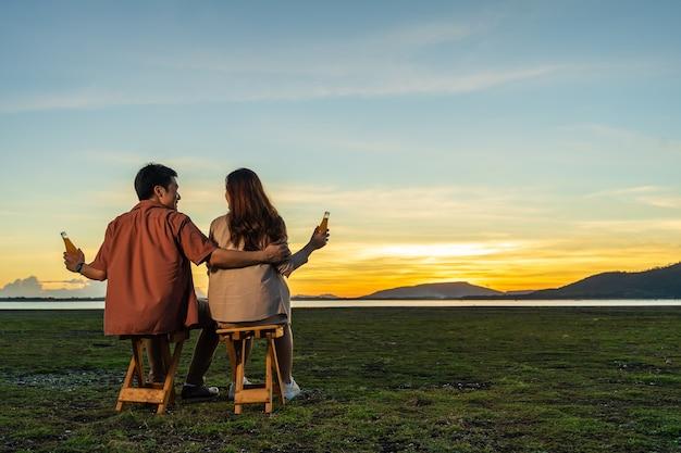 Junges verliebtes paar sitzt und feiert im gras bei sonnenuntergang