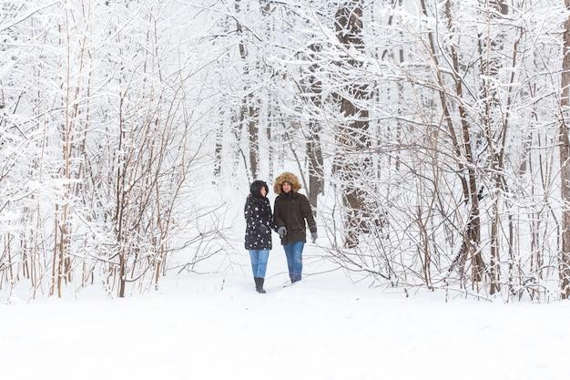 Junges verliebtes paar spaziergänge im verschneiten wald aktive winterferien