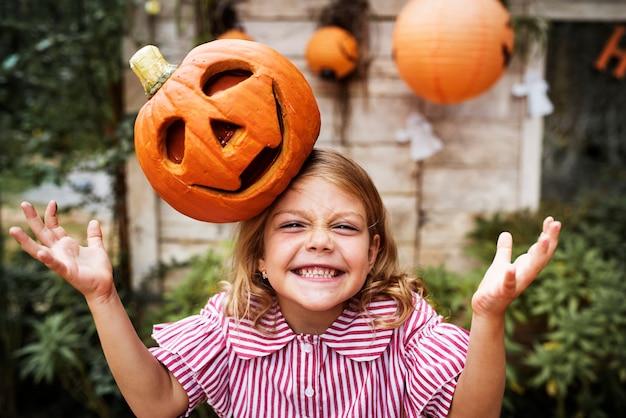 Junges verspieltes mädchen mit ihrer halloween-kürbislaterne
