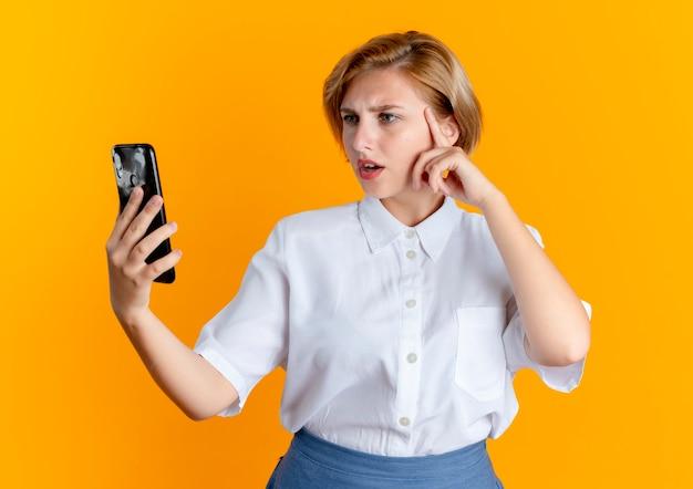 Junges verwirrtes blondes russisches mädchen legt hand auf gesicht, das telefon betrachtet