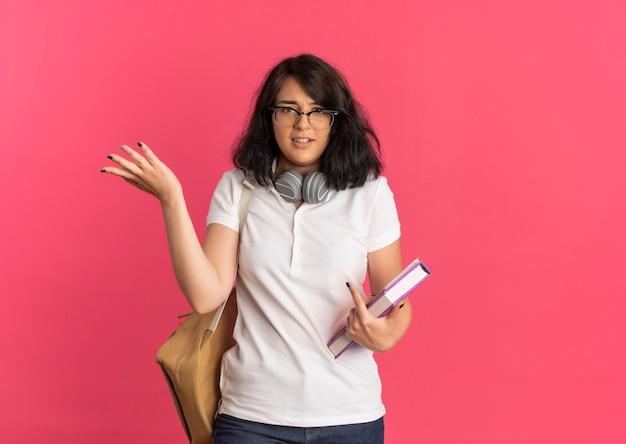 Junges verwirrtes hübsches kaukasisches schulmädchen, das brille und rückentasche mit kopfhörern am hals trägt, hält bücher und hebt hand auf rosa mit kopienraum