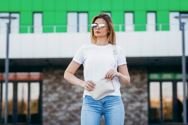 Junges vorbildliches mädchen im weißen t-shirt und in den gläsern mit hüfttasche