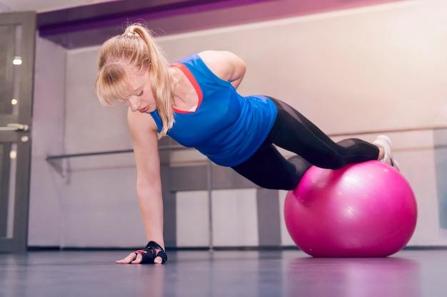 Junges vorbildliches mädchen macht übungen im fitnessstudio. auf einer hand stehen. attraktives blondes fitnessmodell, das liegestütze mit einem fitball, sportkonzept, gesundem lebensstil und fitness durchführt