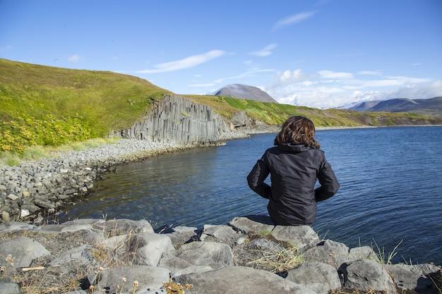 Junges weibchen, das die schönen steinmauern an der küste von olafsfjordur beobachtet