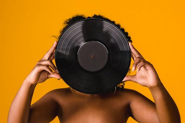 Junges weibliches bedeckungsgesicht des nackten afroamerikaners mit vinylplatte im studio