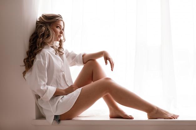 Junges weibliches blondes modell im fensterlicht. frau in der nähe von fenster. träumen sie und entspannen sie sich, zartes mädchen morgens im schlafzimmerfenster