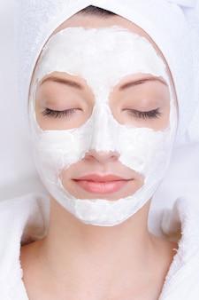 Junges weibliches gesicht mit kosmetischer maske - schönheitssalon