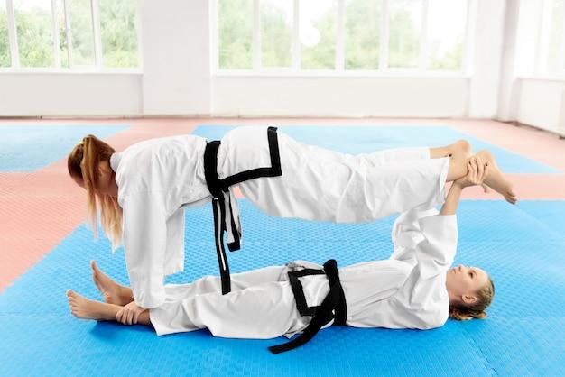 Junges weibliches karate zwei, das vor der ausbildung in der hellen turnhalle ausdehnt.