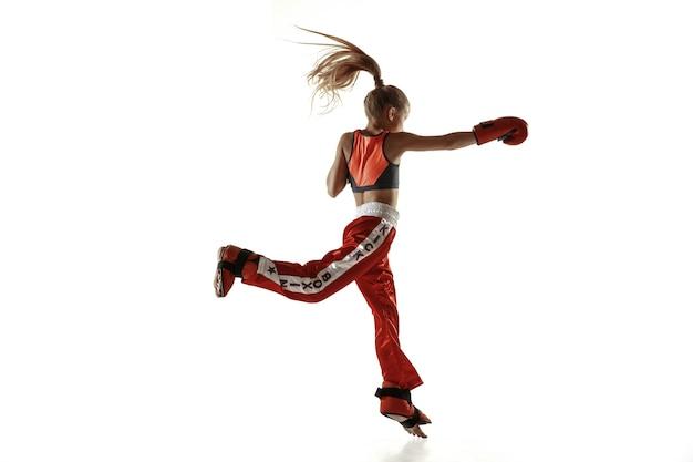 Junges weibliches kickboxen-kämpfertraining lokalisiert auf weißer wand. kaukasisches blondes mädchen in roter sportkleidung, das in den kampfkünsten praktiziert. konzept des sports, gesunder lebensstil, bewegung, aktion, jugend.