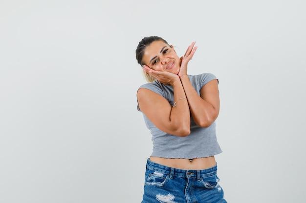 Junges weibliches kissengesicht auf ihren händen in t-shirt, shorts und niedlich aussehend