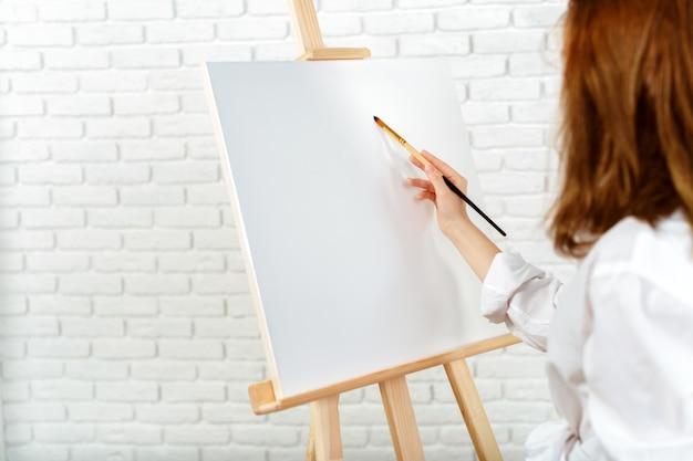 Junges weibliches künstlermalereibild im studio