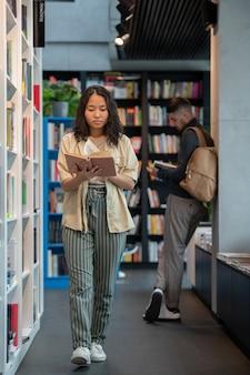 Junges weibliches lesebuch unterwegs in der bibliothek