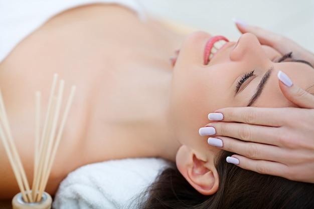 Junges weibliches lügen im badekurortsalon nach verfahren der körpermassage