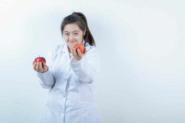 Junges weibliches mädchen in der arztuniform, die rote apfelfrüchte hält.
