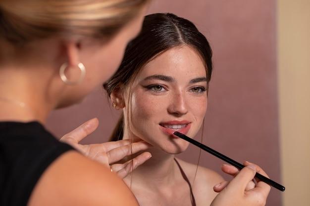 Junges weibliches model, das sich von einem professionellen künstler schminken lässt