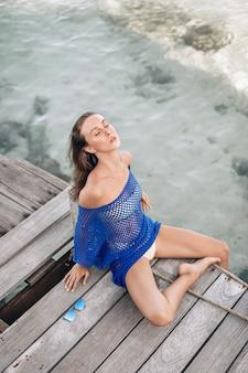 Junges weibliches model sitzt und posiert auf einer holzbrücke mit nach hinten geneigtem kopf, geschlossenen augen und genießt die atmosphäre