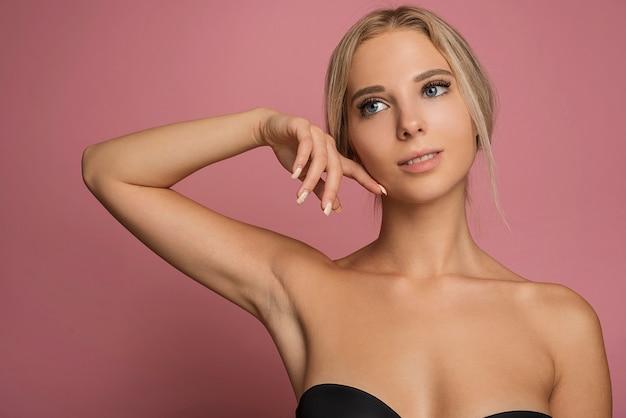 Junges weibliches modell, das auf rosa hintergrund aufwirft