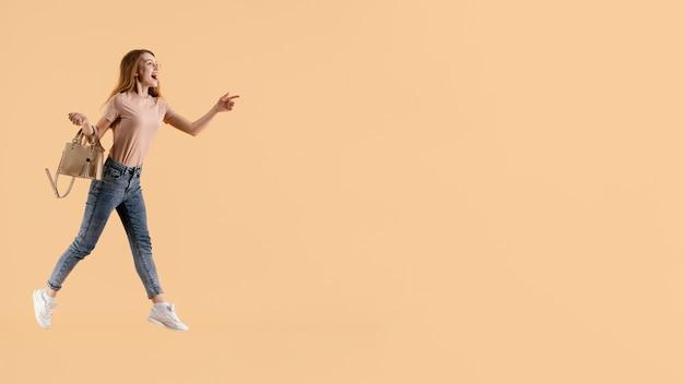 Junges weibliches modell mit handtaschenspringen