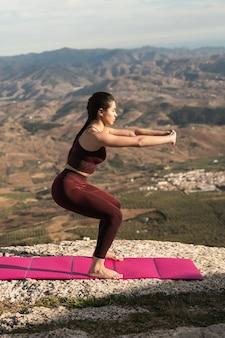 Junges weibliches übendes yoga im freien