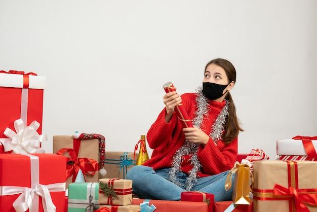 Junges weihnachtsmädchen mit schwarzer maske, die party-popper hält, der herum geschenke auf weiß sitzt