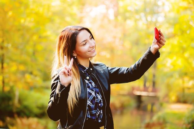 Junges weißes mädchen, das eine handykamera für ein selfie verwendet
