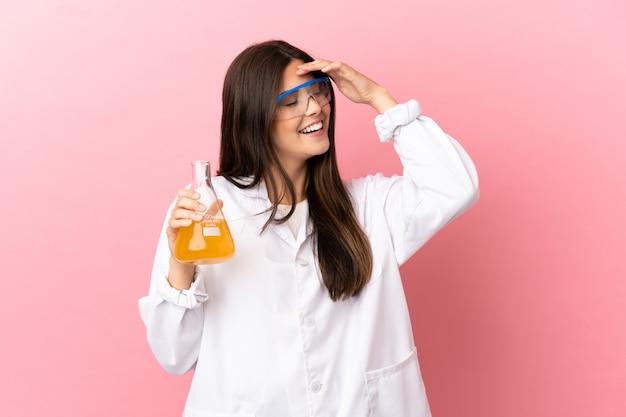 Junges wissenschaftliches mädchen über isoliertem rosa hintergrund, das viel lächelt