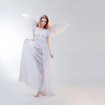 Junges, wundervolles blondes mädchen im bild eines engels mit weißen flügeln.