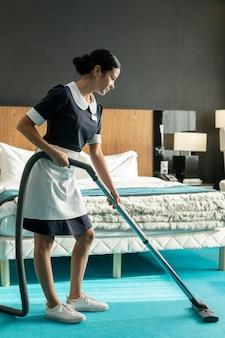 Junges zeitgenössisches brünettes zimmermädchen in uniform mit staubsauger beim reinigen des blauen bodenbelags in einem der hotelzimmer