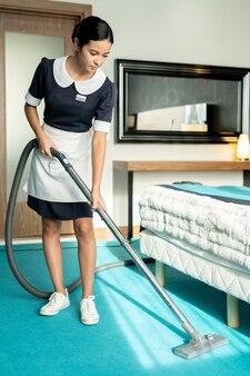 Junges zimmermädchen mit staubsauger in einem der hotelzimmer
