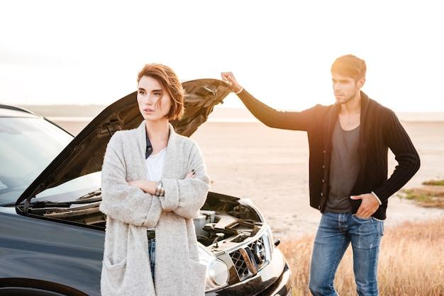 Junges zufälliges paar, das draußen in der nähe eines kaputten autos mit offener haube steht