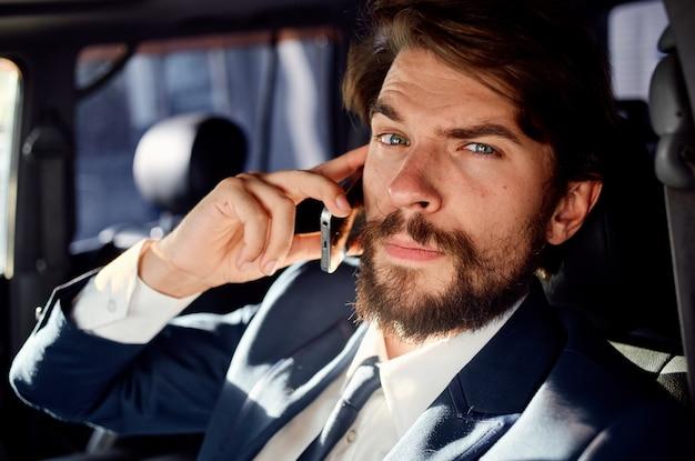 Jungfrau mann, der am telefon spricht, während er ein auto im salon fährt