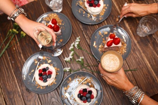 Junggesellenabschied, mädchenhände mit getränken und süßen kuchen mit sommerbeeren auf einem holztisch. party, süßer tisch. sommer bieten desserts im restaurant.