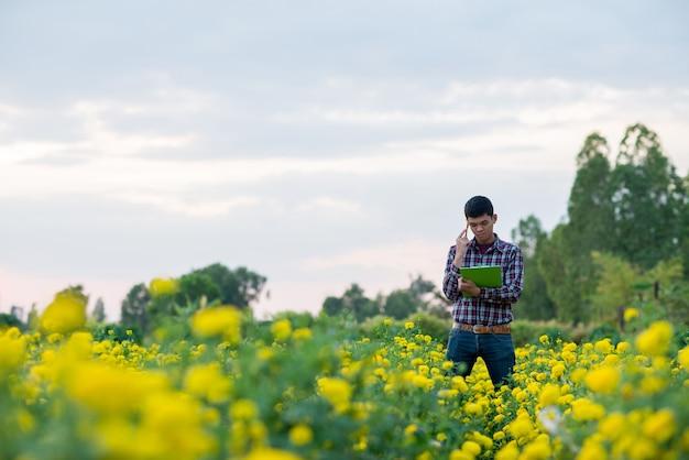 Junglandwirt mit dem bart, der tablette auf dem gebiet hält. saisonale landwirtschaftliche arbeiten
