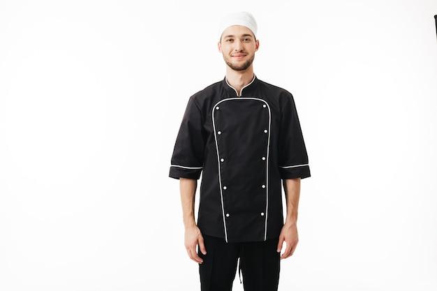 Jungmann koch in schwarzer uniform und weißer mütze verträumt